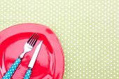 empty red plate and knife, fork