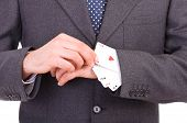 Businessman with playing cards hidden under sleeve.