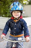 picture of tricycle  - Boy on tricycle smiling and wearing helmet safely - JPG