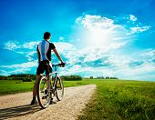 stock photo of biker  - Rear View of a Young Man With Bicycle on Summer Nature Background - JPG