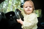 Little blond girl driving car