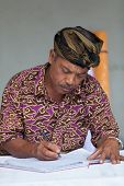 Balinese Man Maintain Records In Register Book