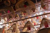 picture of rafters  - In the Man Mo Temple on Hollywood Road in Hong Kong coils of incense burning overhead in the rafters over the worshippers infuse the air with fragrant smoke - JPG