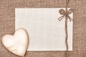 foto of canvas  - Valentine card with wooden heart and canvas on burlap background