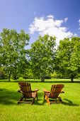picture of lawn chair  - Two wooden adirondack chairs on lush green lawn with trees - JPG
