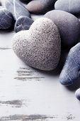 Grey stone in shape of heart, on color wooden background