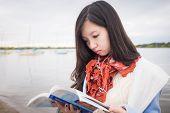 Girl Reading Book Near Lake