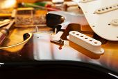 Sunburst electric guitar body on guitar repair desk. Electric guitar on a guitar repair work shop de