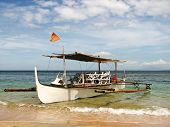 Wooden Outrigger Boat on a Beach Shore