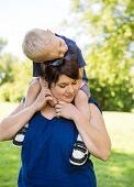 Happy mid adult woman carrying son on shoulders in park