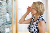 Mature woman trying on eyeglasses in optician store