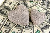 Love and money concept. Heart-shaped stone and American currency close up.