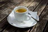 Cup of espresso on a wooden table, outdoor setting