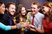 Group of friends toasting with flutes of champagne at party
