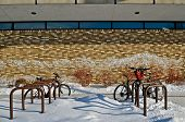 To bicycles park in front of a brick building which has remains of snow blowing