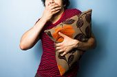 Young Man Clutching Cushion While Watching Scary Movie
