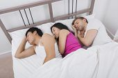 Young woman sleeping with two men in bed