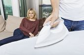 Man ironing shirt while woman relaxing on sofa at home