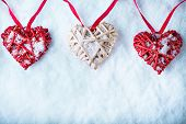 Three  beautiful romantic vintage hearts are hanging on a red band on a white snow background. Love and St. Valentines Day concept.