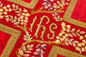 Closeup of antique 19th century vestment chasuble with the letters IHS (Iesus Hominum Salvator) whic
