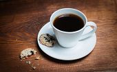 Coffee cup and saucer on a wooden table. Dark background. Cup of espresso and cookies. Coffee cup an