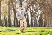 Overjoyed senior playing air guitar in park