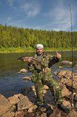 Fisherman Holding A Large Fish Salmon.