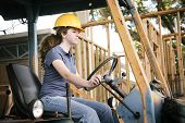 Young female construction apprentice learning to drive heavy equipment.