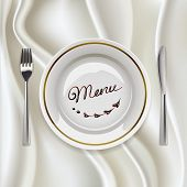 Plate with cutlery on glossy tablecloth
