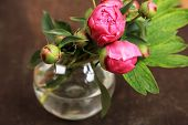 Beautiful peonies in vase on  wooden  background