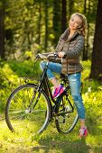 Cheerful teenage girl listens music on a bicycle outdoors