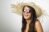 Pretty young girl smiling with straw hat and sun glasses in the studio