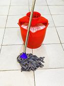 Red Bucket With Foamy Water And Mop The Floor