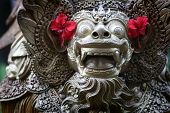 Balinese statue with hibiscus flower