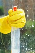 Hand In Rubber Glove Cleans Window By Spray