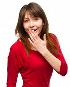 Young woman is covering her mouth in astonishment, isolated over white