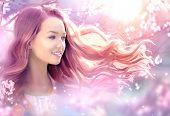 Fantasy Girl with long pink blowing hair. Spring or summer beauty teen girl with flowers. Fashion Ar