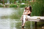 Happy young family with kids heaving fun near pond