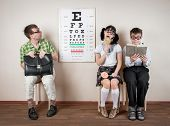 Three funny person wearing spectacles in an office at the doctor