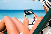 Woman on vacation lies in a sun lounger on the beach with a tablet in hands (copy space display).