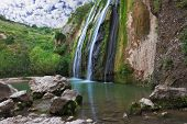 Three parallel streams of water running down the steep slope and fall in oval pool. Three-jet scenic