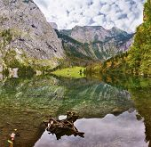 Cloudy day on the lake. Magic reflection in German lake Koenigssee. Clouds and mountains reflected i