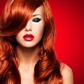 Portrait  of beautiful  woman with long red hairs and red lips. Calm face  of adult pretty girl