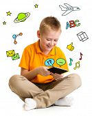 Kid boy sitting with tablet computer and learning or playing with great interest