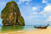 Traditional thai longtail boat landing on sea coast. Krabi, Andaman Sea, Thailand