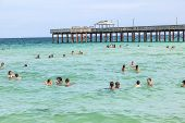 People Enjoy Swimming At  Pier On A Beach In Miami
