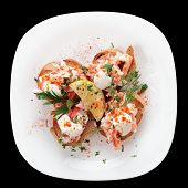 Crab meat with toast, sauce and fresh herbs in plate, isolated on black