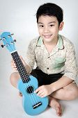 Asian Child  With His Ukulele