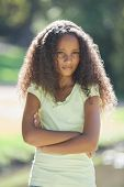 Young girl frowning with arms crossed in the park on a sunny day