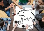 People sitting around table drinking coffee with page showing loan shark doodle